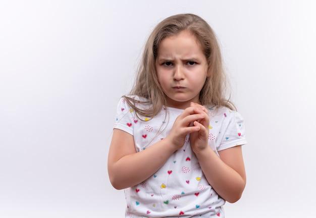 Smutna mała uczennica na sobie białą koszulkę, trzymając się za ręce razem na na białym tle