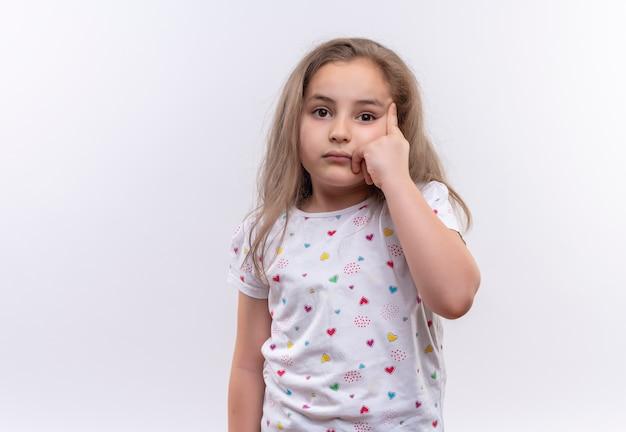 Smutna mała uczennica ubrana w białą koszulkę kładzie palec na oku na na białym tle