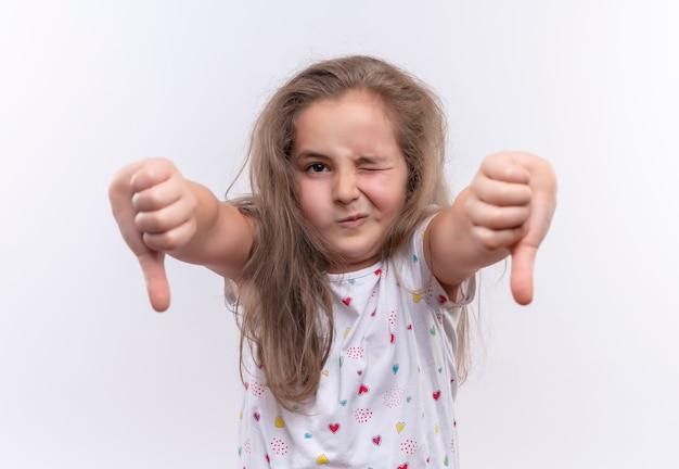 Smutna mała uczennica ubrana w białą koszulkę mruga z kciukami w dół na na białym tle