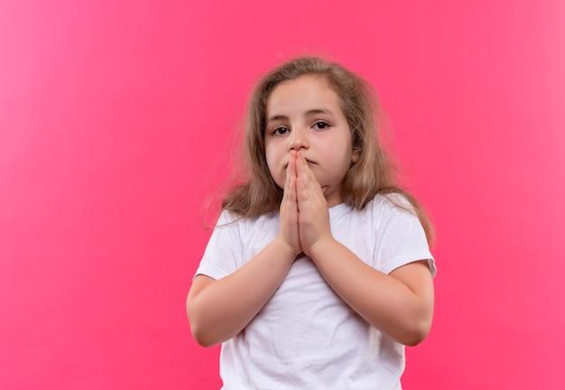 Smutna mała uczennica ubrana w białą koszulkę przedstawiająca gest modlitwy na na białym tle różowym tle