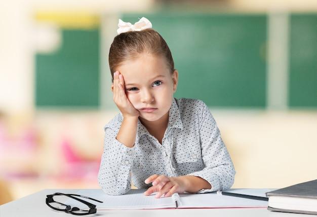 Smutna mała uczennica w klasie na tle tablicy