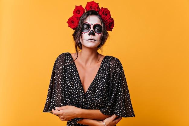 Smutna martwa panna młoda z makijażem zombie stojącej na żółtej ścianie. elegancka kobieta łacińskiej z różami we włosach przygotowuje się do halloween.