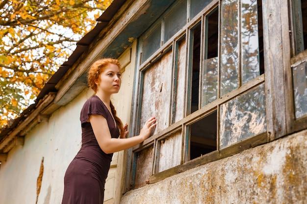 Smutna miedzianowłosa dziewczyna stoi blisko łamanego okno, pojęcia ubóstwo i niedola