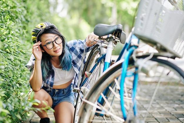 Smutna młoda azjatka w kasku sprawdzająca złamany bicyle przemówiła