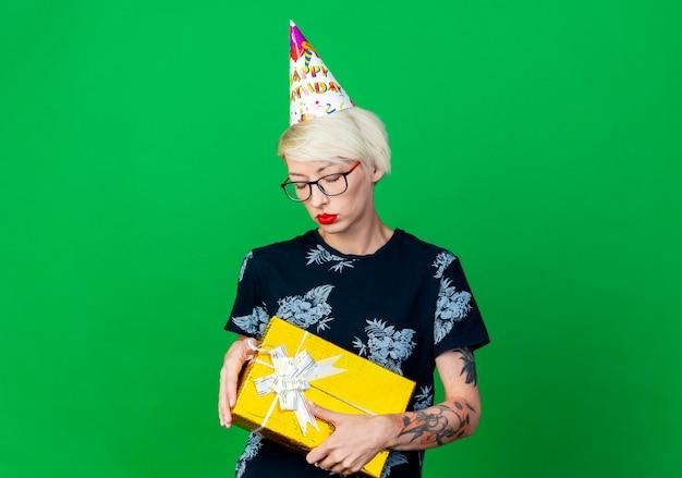 Smutna młoda blondynka strona kobieta w okularach i czapce urodzinowej, trzymając pudełko z zamkniętymi oczami na białym tle na zielonej ścianie z miejsca na kopię