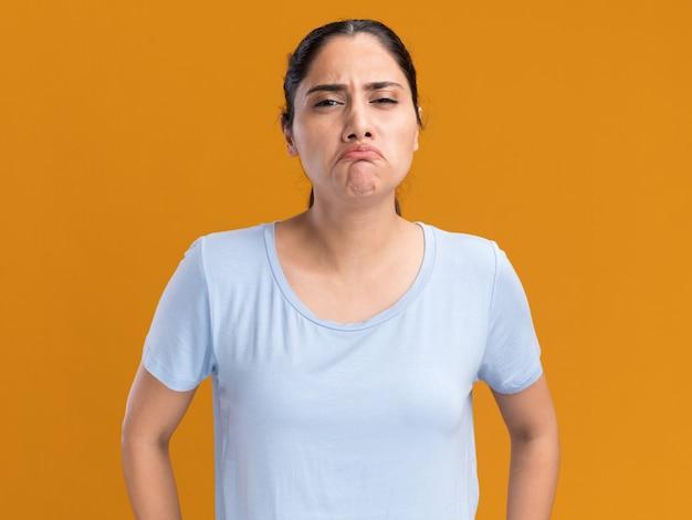 Smutna młoda brunetka kaukaska dziewczyna odizolowana na pomarańczowej ścianie z miejscem na kopię