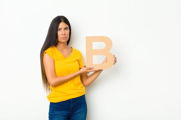 Smutna młoda brunetka kobieta trzyma literę b alfabetu, aby utworzyć słowo lub zdanie