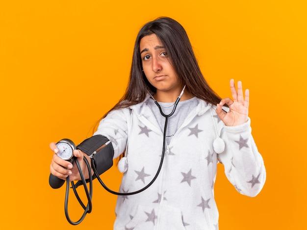 Smutna młoda chora dziewczyna mierzy własne ciśnienie za pomocą ciśnieniomierza pokazującego dobry gest na białym tle na żółtym tle