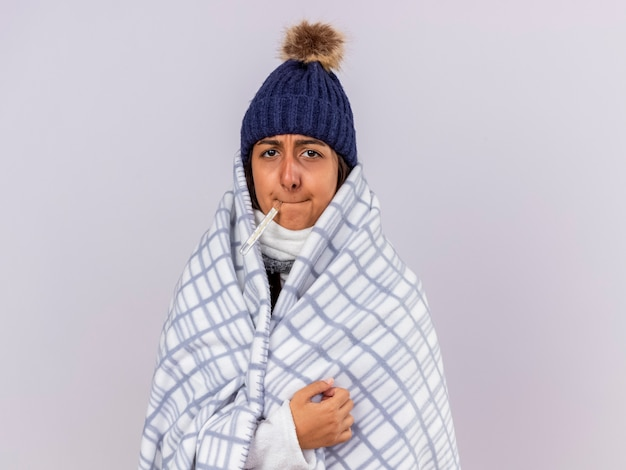 Smutna młoda chora dziewczyna na sobie czapkę zimową z szalikiem zawiniętym w kratę, umieszczając termometr w ustach na białym tle