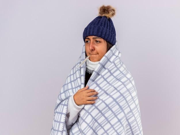 Smutna młoda chora dziewczyna patrząc z boku w czapce zimowej z szalikiem zawiniętym w kratę wkładając termometr do ust