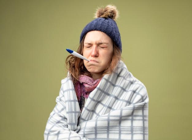 Smutna młoda chora dziewczyna ubrana w białą szatę i czapkę zimową z szalikiem owiniętym w kratę wkładającą termometr do ust odizolowany na oliwkowej zieleni