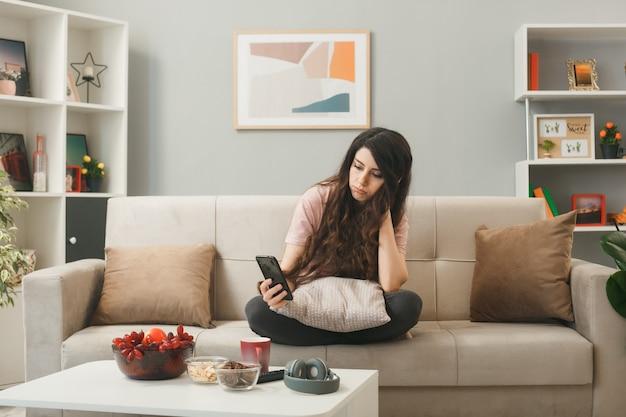 Smutna młoda dziewczyna trzyma telefon i patrzy na telefon, siedząc na kanapie za stolikiem kawowym w salonie