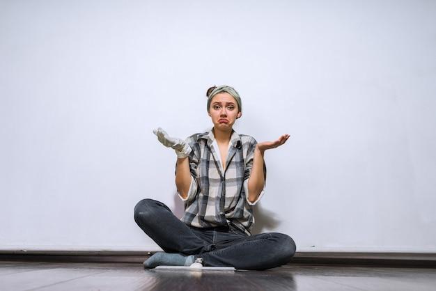 Smutna młoda dziewczyna w gumowych rękawiczkach siedzi na podłodze, zmęczona robieniem napraw