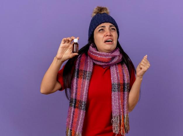 Smutna młoda kaukaska chora dziewczyna w czapce zimowej i szaliku trzymająca lekarstwo w szkle patrząc w górę zaciskającą pięść odizolowaną na fioletowym tle z miejscem na kopię