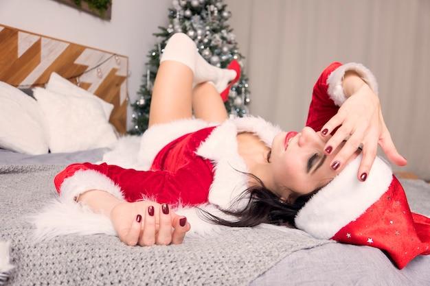 Smutna młoda kobieta cierpi na kaca po bożym narodzeniu. piękna brunetka w stroju świętego mikołaja leży na łóżku i trzyma głowę na tle choinki. nowy rok rano.
