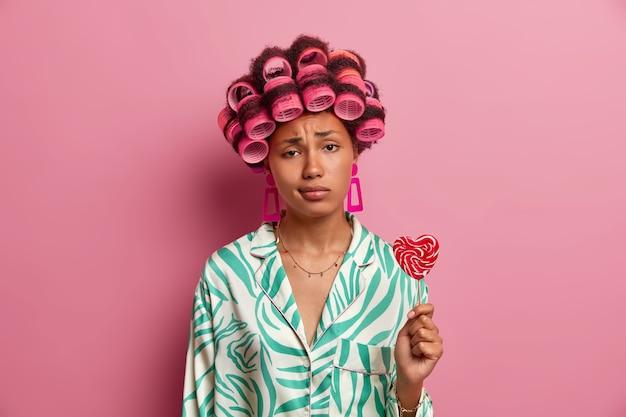 Smutna młoda kobieta ma trwałe włosy, wygląda nieszczęśliwie, nosi wałki do włosów, ubrana jest w zwykłe ciuchy, trzyma słodkiego lizaka, spędza czas dla siebie, dbając o swoją urodę, odizolowana na różowej ścianie