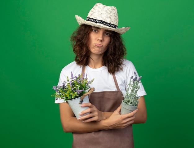 Smutna młoda kobieta ogrodnik w mundurze na sobie kapelusz ogrodniczy trzyma i krzyżuje kwiaty w doniczkach