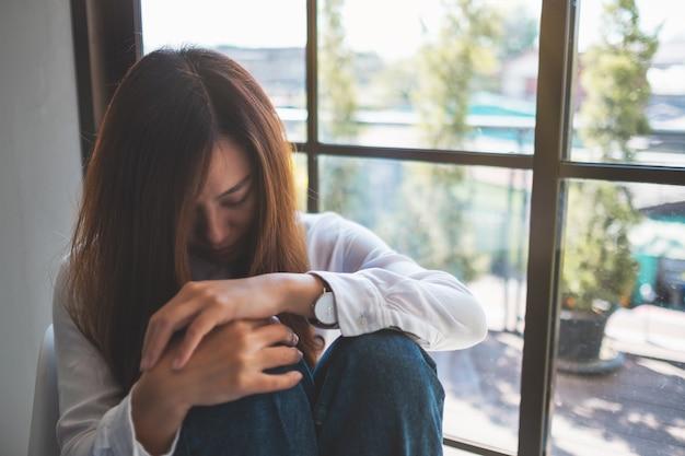 Smutna młoda kobieta siedząca samotnie w pokoju
