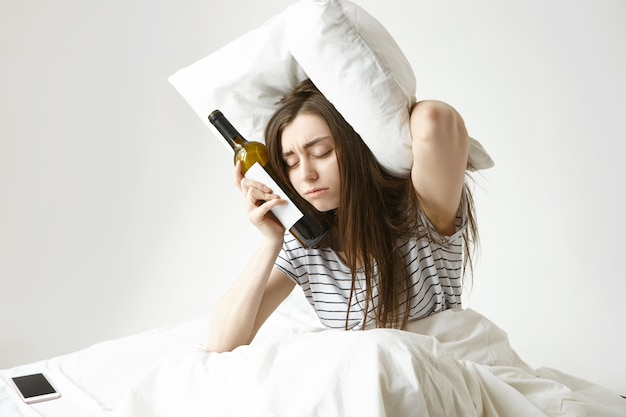 Smutna młoda kobieta siedzi na łóżku cierpiąca na kaca po nocnej imprezie w klubie, ma senny zmęczony wygląd, ma zamknięte oczy, trzyma butelkę wina i poduszkę, próbuje zakryć uszy przed hałasem