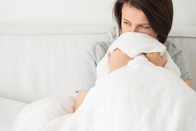 Smutna młoda kobieta siedzi na łóżku w domu, z miejsca kopiowania