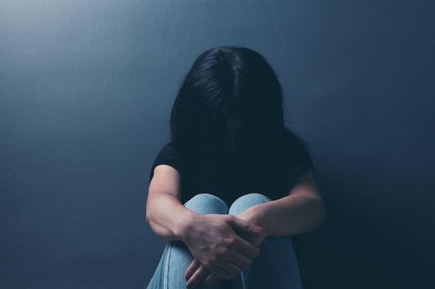 Smutna młoda kobieta siedzi na podłodze