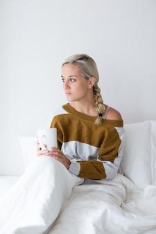 Smutna młoda kobieta siedzi w łóżku pod kocem
