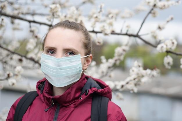 Smutna młoda kobieta w ochronnej medycznej twarzy masce. kwitnące drzewo na tle. alergia wiosenna.
