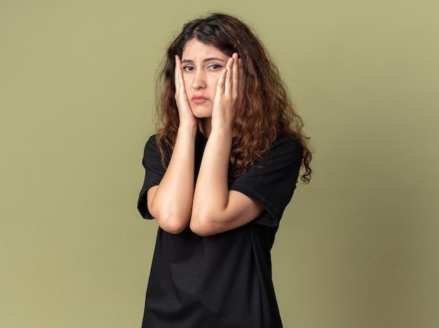Smutna młoda ładna dziewczyna trzymająca ręce na twarzy