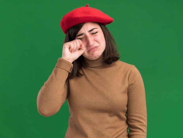 Smutna młoda ładna kaukaska dziewczyna w beretowym kapeluszu płacze, kładąc pięść na powiece na zielonej ścianie z miejscem na kopię