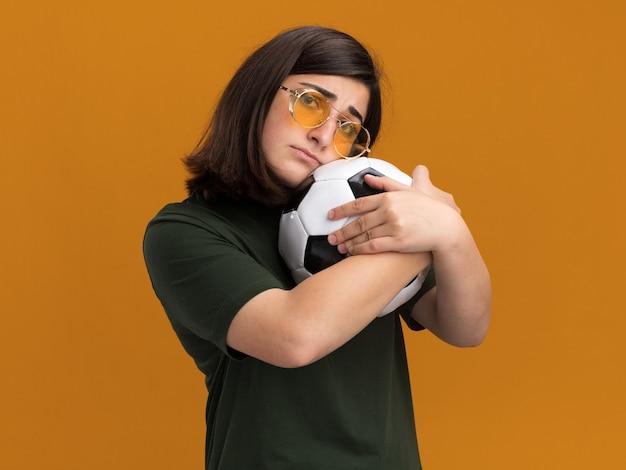 Smutna młoda ładna kaukaska dziewczyna w okularach przeciwsłonecznych przytula piłkę odizolowaną na pomarańczowej ścianie z miejscem na kopię