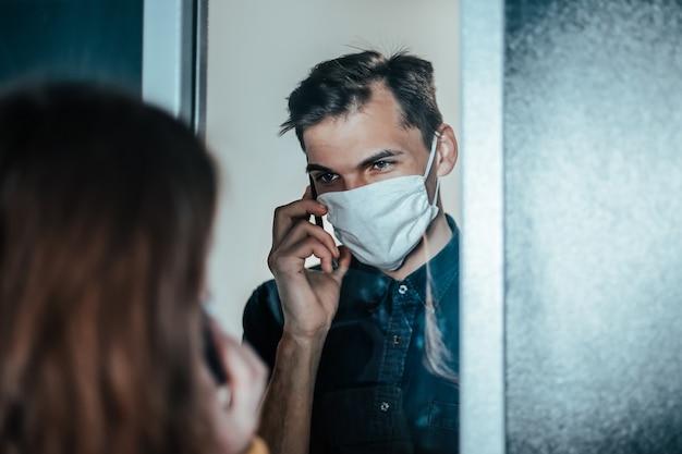 Smutna młoda para w maskach ochronnych, patrząc na siebie.