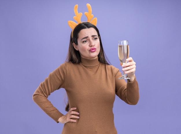 Smutna młoda piękna dziewczyna ubrana w brązowy sweter z świąteczną obręczą do włosów, trzymając i patrząc na kieliszek szampana, kładąc rękę na biodrze na białym tle na niebieskim tle