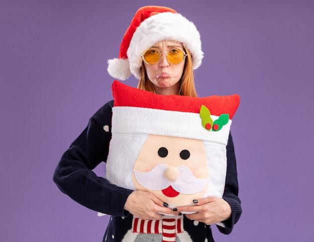 Smutna młoda piękna dziewczyna ubrana w świąteczny sweter i kapelusz w okularach trzymająca świąteczną poduszkę odizolowaną na fioletowej ścianie
