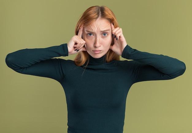 Smutna, młoda rudowłosa rudowłosa dziewczyna z piegami kładzie ręce na skroniach na oliwkowej zieleni