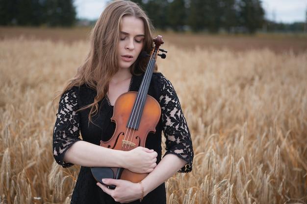 Smutna, młoda skrzypaczka ze spuszczonymi oczami delikatnie przyciska do niej swoje skrzypce