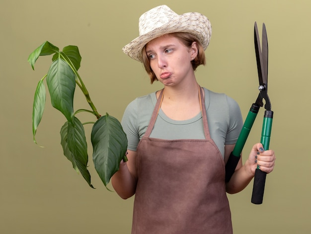 Smutna młoda słowiańska ogrodniczka na sobie kapelusz ogrodniczy trzymając nożyczki ogrodnicze i roślin na oliwkowej zieleni