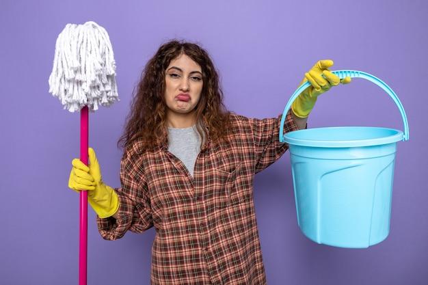 Smutna młoda sprzątaczka w rękawiczkach, trzymająca mopa z wiadrem na fioletowej ścianie