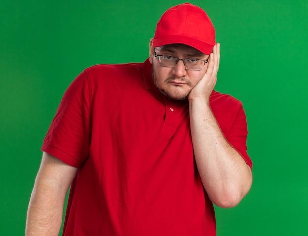 Smutna nadwaga młody doręczyciel w okularach optycznych kładzie rękę na twarzy odizolowanej na zielonej ścianie z miejscem na kopię