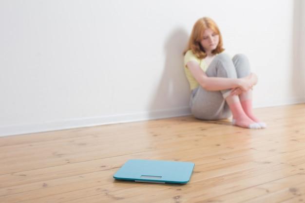 Smutna nastolatek dziewczyna z skala na drewnianej podłoga