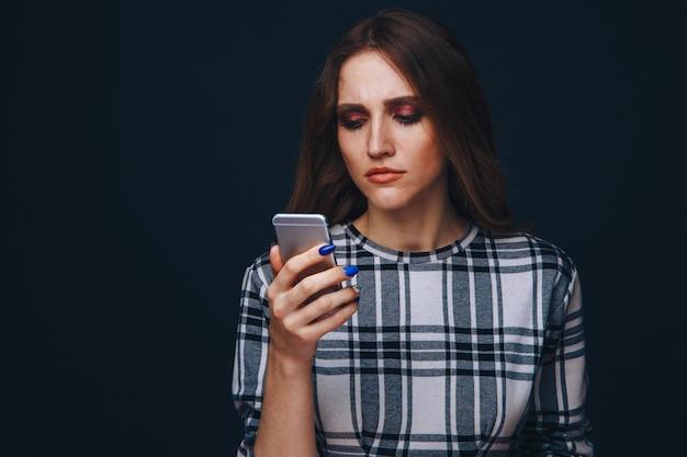 Smutna nastolatka będąca ofiarą cyberprzemocy w internecie siedząca na kanapie w salonie w domu