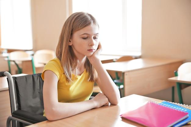 Smutna nastolatka na wózku inwalidzkim przy biurku w klasie