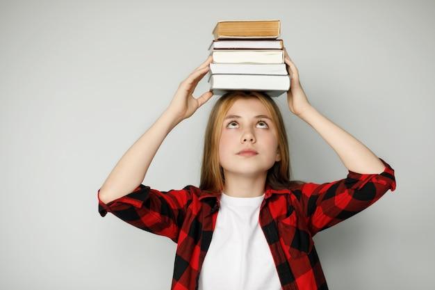 Smutna nastolatka trzyma wiele książek na głowie trudności edukacyjne