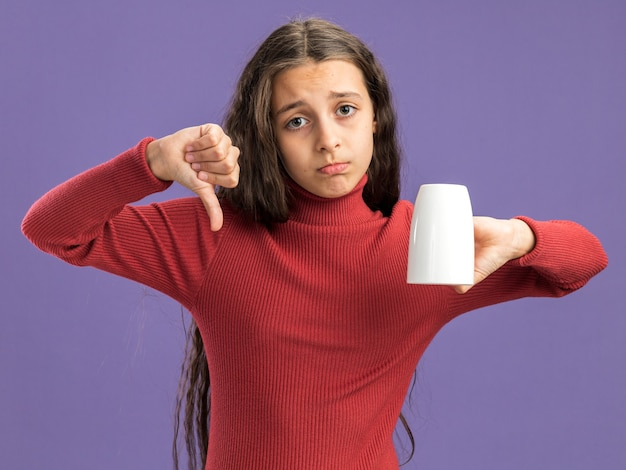 Smutna nastolatka trzymająca filiżankę herbaty do góry nogami, patrząc na przód pokazujący kciuk w dół odizolowany na fioletowej ścianie