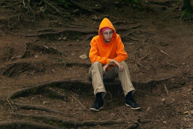Smutna nastolatka w bluzie z kapturem siedzi na naturalnym tle