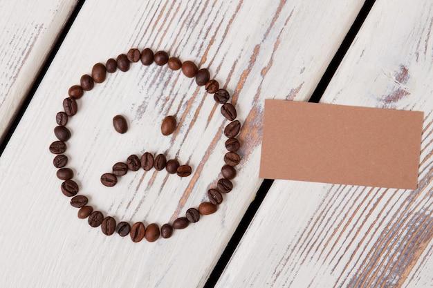 Smutna nieszczęśliwa buźka z ziaren kawy. pusty papier beżowy dla copyspace na białym drewnie.