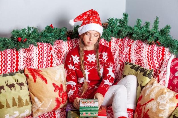 Smutna nieszczęśliwa dziewczyna w santa hat otwiera świąteczne pudełka na prezenty w ozdoby sylwestrowe
