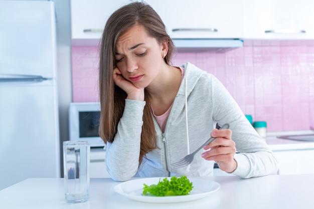 Smutna, nieszczęśliwa młoda kobieta jest zmęczona dietą i nie chce jeść ekologicznej, czystej zdrowej żywności