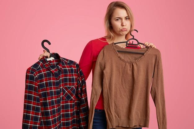 Smutna niezadowolona kaukaska kobieta zaciska usta, trzyma dwie koszulki, wieszaki w centrum handlowym, niezadowolenie z wysokiej ceny, odizolowane na różowo