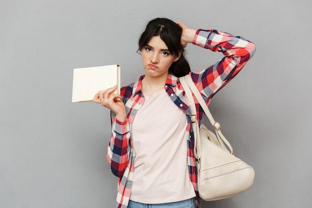Smutna niezadowolona młoda dama trzyma książkę.