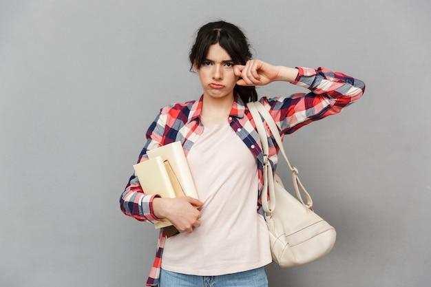 Smutna niezadowolona młoda dama trzyma książki.